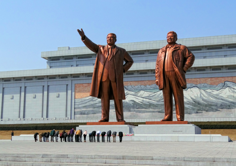 The Mansudae Grand Monument in Pyongyang depicting Kim Il-sung and Kim Jong-il, with visitors paying homage.